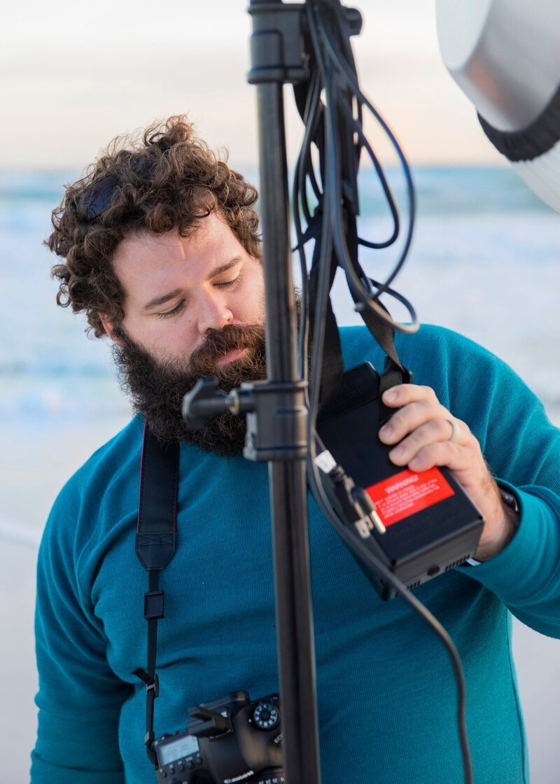 Joshua Cox- Joshua & Inez Photography - Joshua setting up lighting equipment on the beach