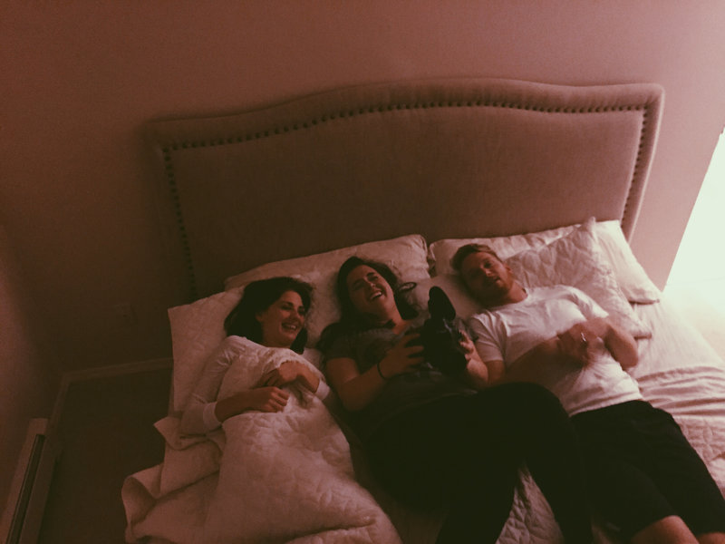 lauren roberts lays in bed with couples laughing
