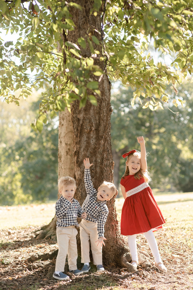 three siblings are standing under a tree and raising their hands to be silly for family photos in Nashville Tennessee