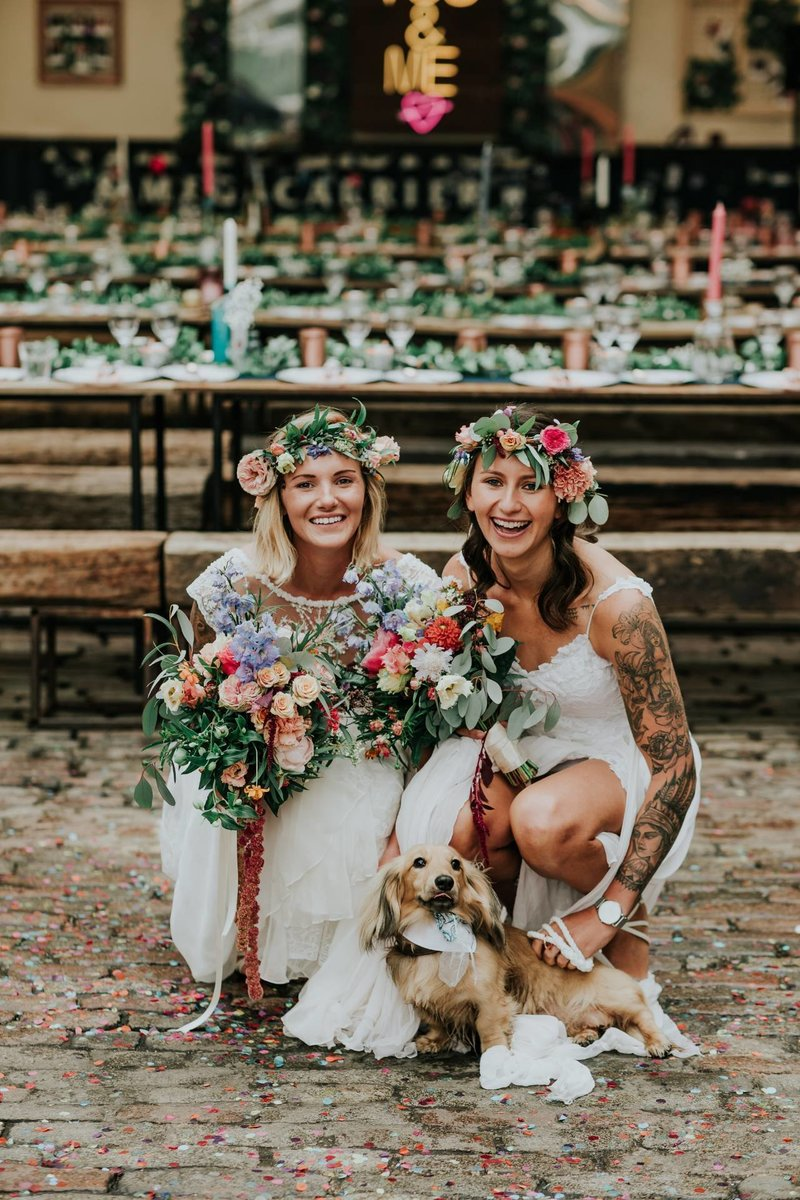 two brides holding bouquets with dog