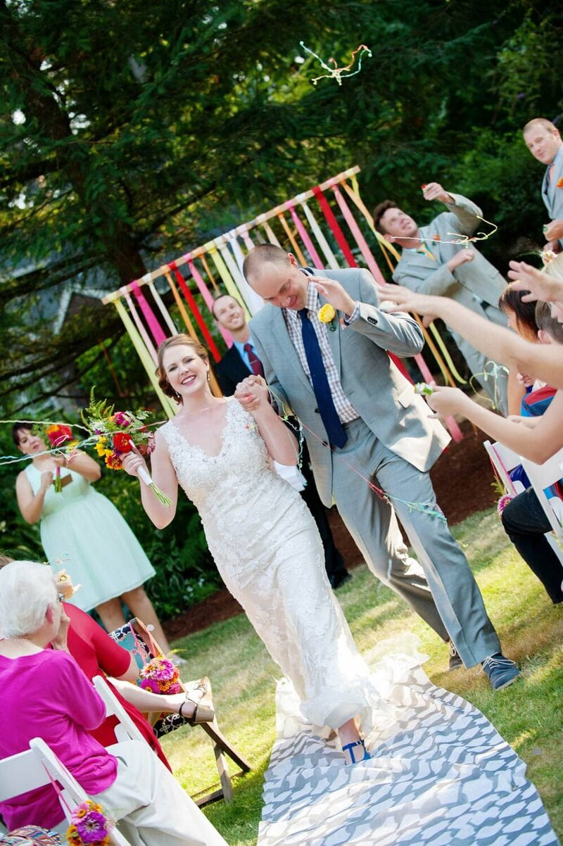 Happy bride and groom skip exiting the ceremony colorful flowers and ribbons in the air