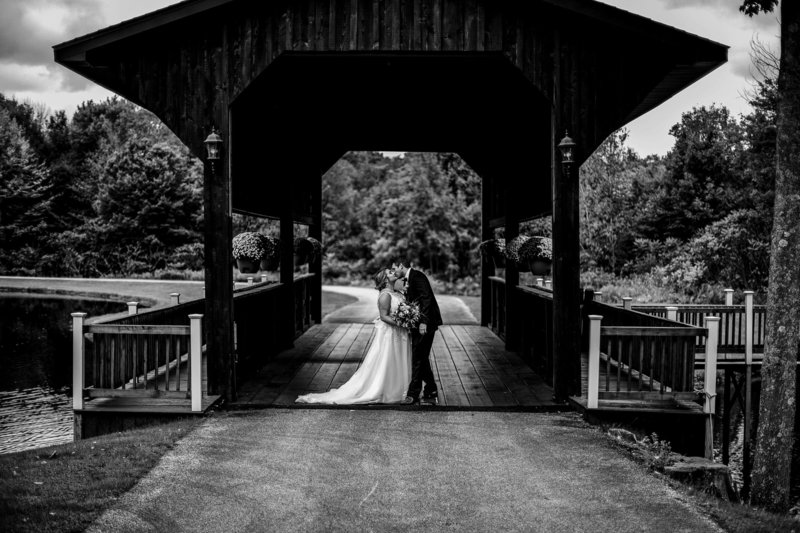 Bride and groom kissing on the covered bridge at Majestic Woods
