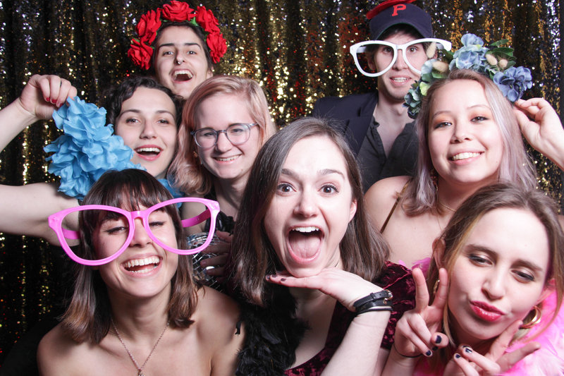 eight people posing and having a blast in the photobooth