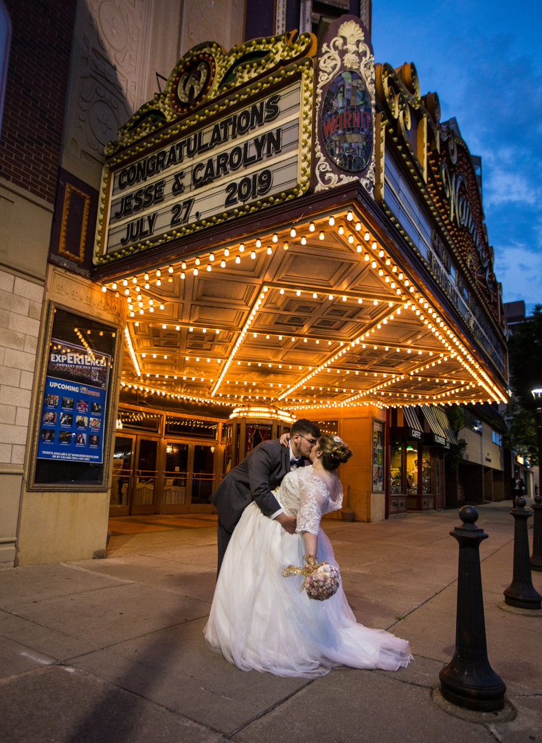 bride and groom kiss under the marquee at the Warner Theatre in Erie, PA