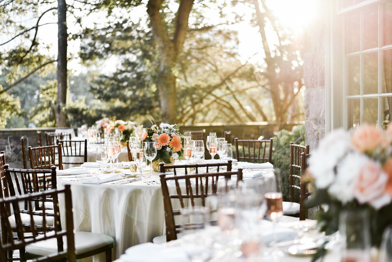 Sunlit terrace at graydon hall with coral florals and wooden chair for this gorgeous summer wedding decor