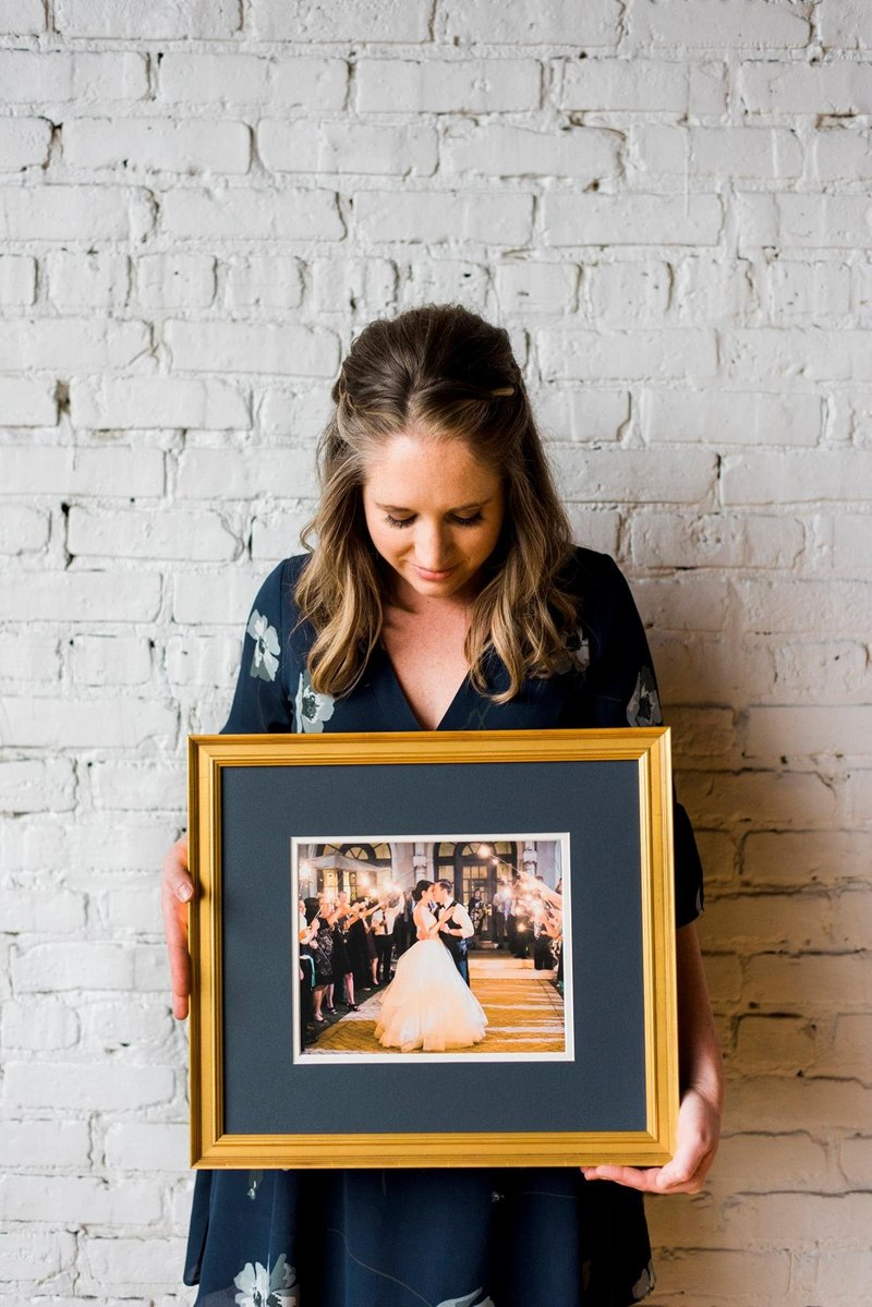 Owner of Artistrie Co. holding a framed and matted wedding photo.