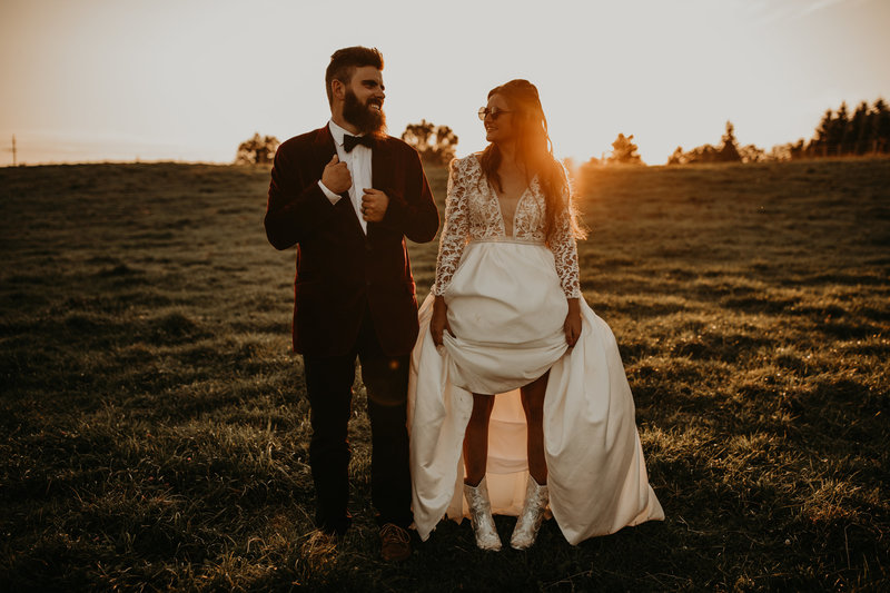 bride and groom smiling at each other while standing in field