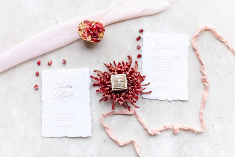 flat lay with wedding invites and pomegranates and pink ribbon