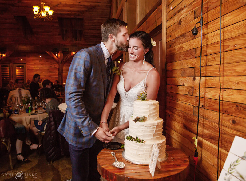 Cute couple kisses as they cut their wedding cake at Mountain View Ranch Wedding Reception in the Barn