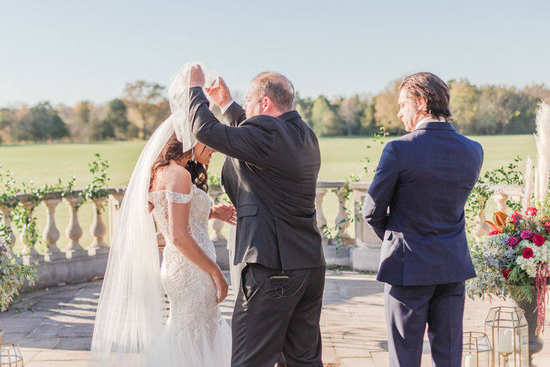father lifting brides veil at ceremony at great marsh estate wedding in northern virginia by costola photography