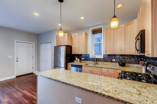 Medill Kitchen speckled stone countertops natural wood cabinetry and chrome and wood accessories