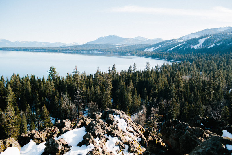 Lake Tahoe shoreline with homes and snow covered mountains.