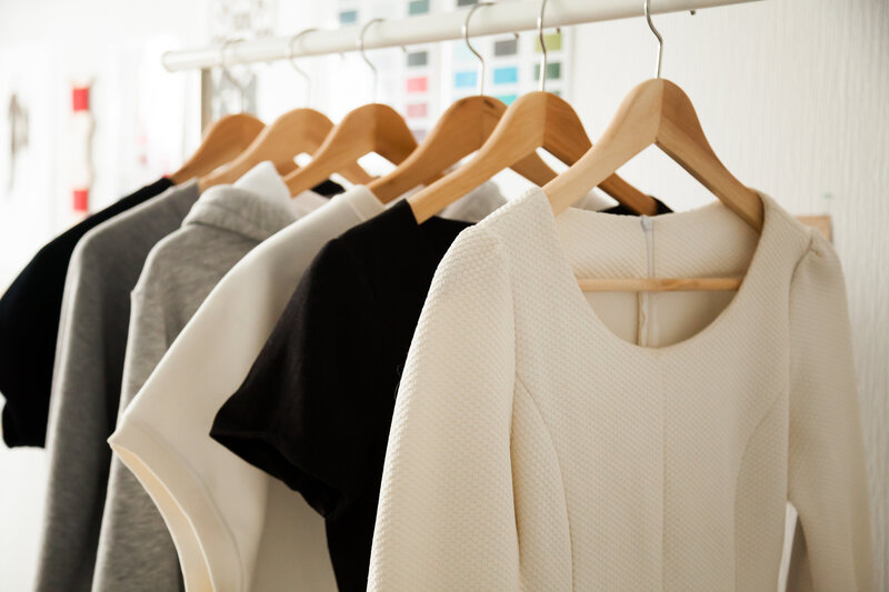 A collection of black, white and gray blouses on  wooden hangers