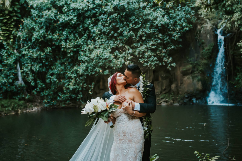 bride and groom kissing next to water