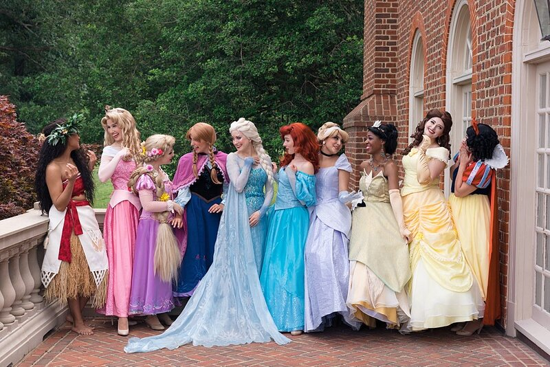 Richmond Princesses gathered together in rainbow order, giggling with each other. Moana, Sleeping Beauty, Rapunzel, Anna, Elsa, Ariel, Cinderella, Tiana, Belle, and Snow White.