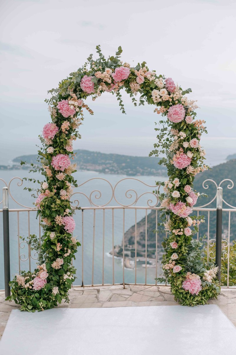 pink and green arch for a wedding ceremony in chateau de la chévre d'or in eze sur mer in south of france