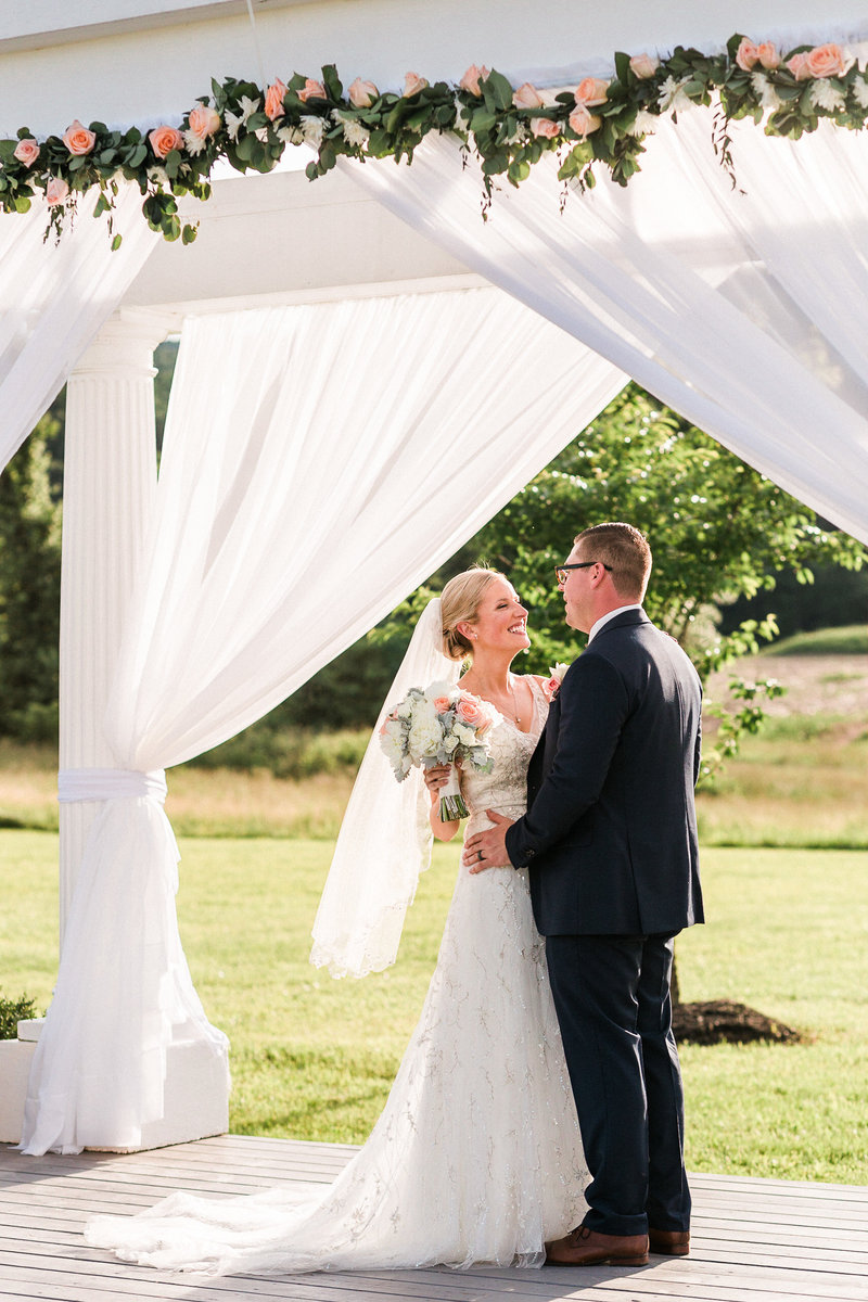 Bride in a white dress and groom in a black tux under a covered porch with white curtains
