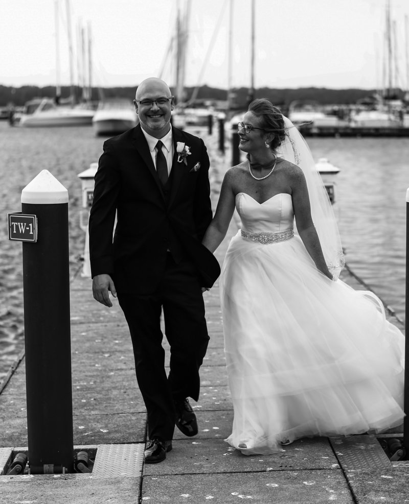Bride and groom hold hands while walking along a dock at the Erie Yacht Club