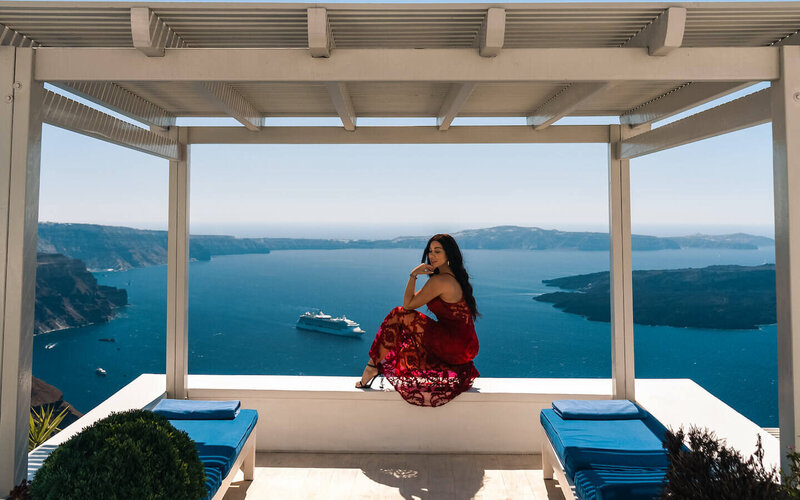 Isabella sitting on ledge in red dress in Greece - luxury travel blogger