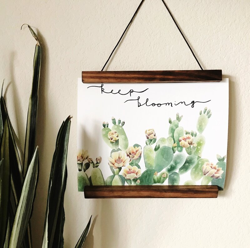 "Art print of plants and ""keep blooming"" quote hanging on wall"