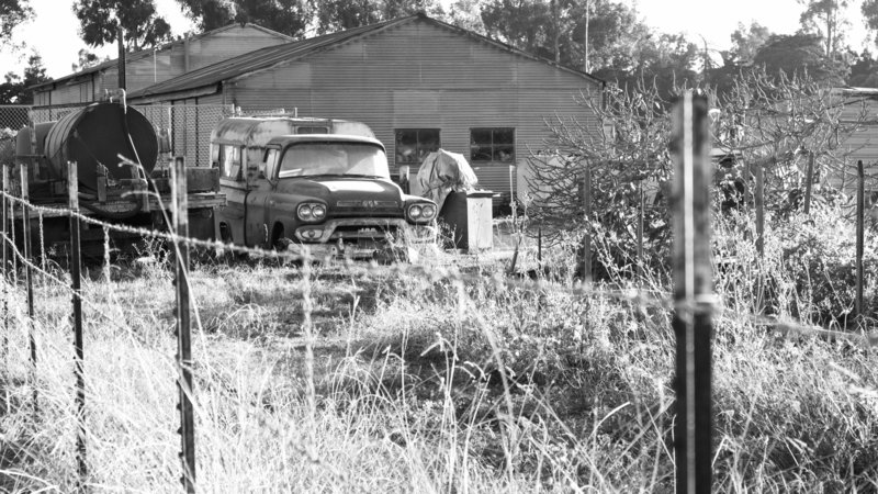 Black and white photo of vintage GMC truck and old metal farm building