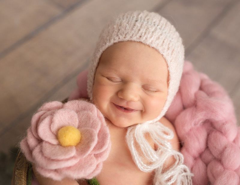 Smiling newborn girl posed  in our Rochester NY studio.