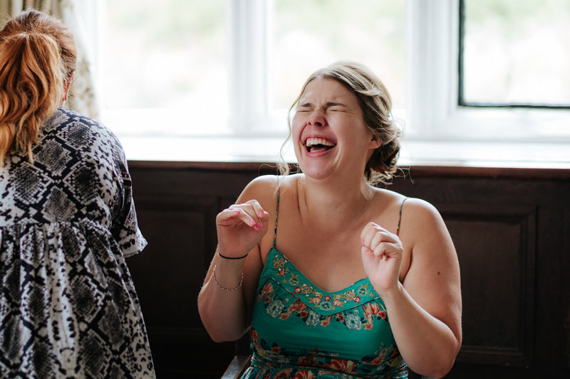 bride laughs and waves her hands in excitement on the morning of her wedding as she's getting ready