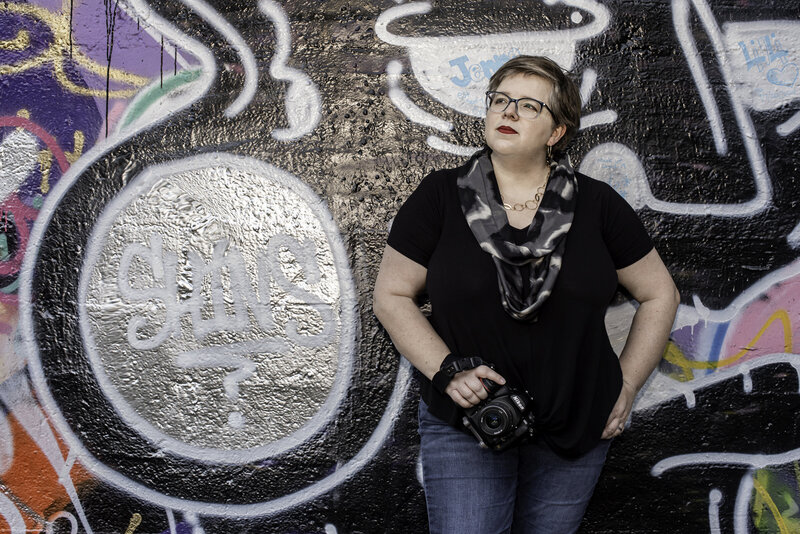 photographer posing with camera in front of graffiti wall