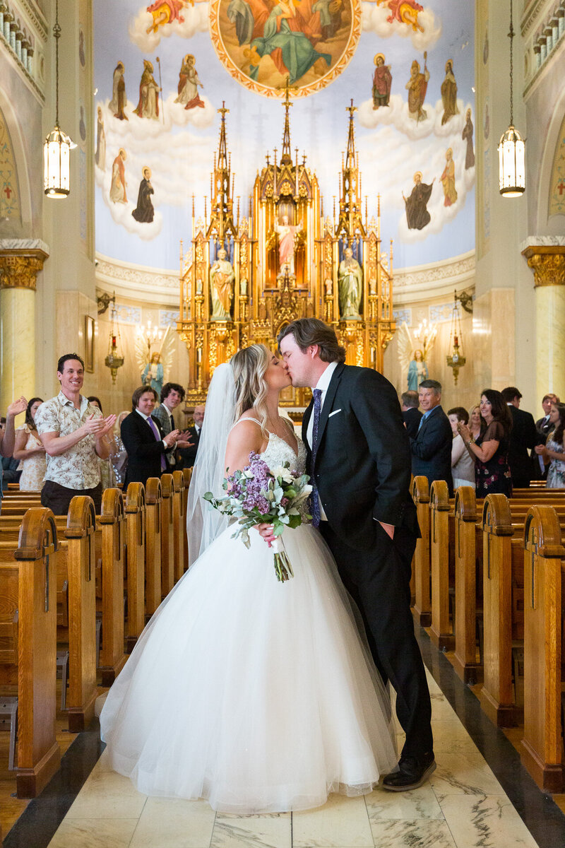 bride and groom kiss at st. john cantius church