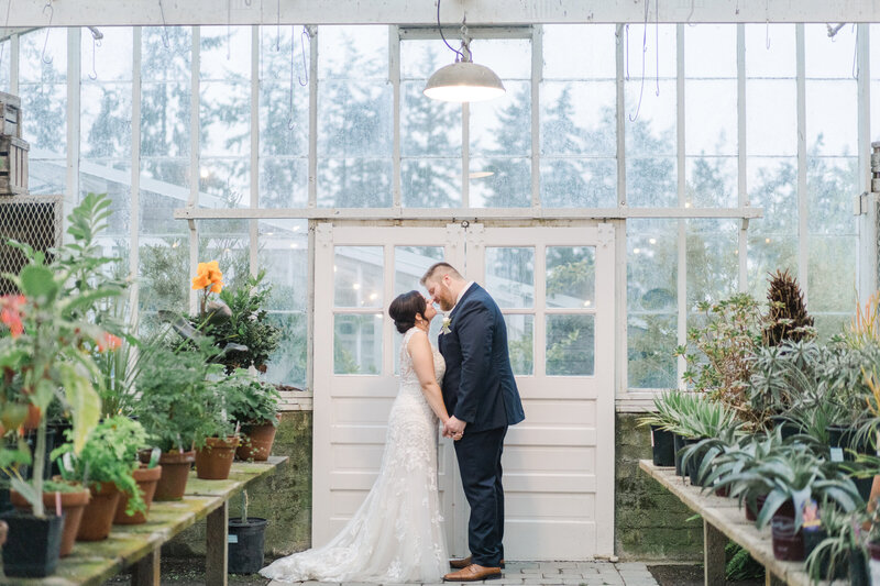 bride and groom face each other and kiss in a greenhouse at christianson's farm