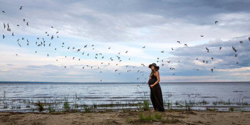 expectant mom on beach with birds flying by