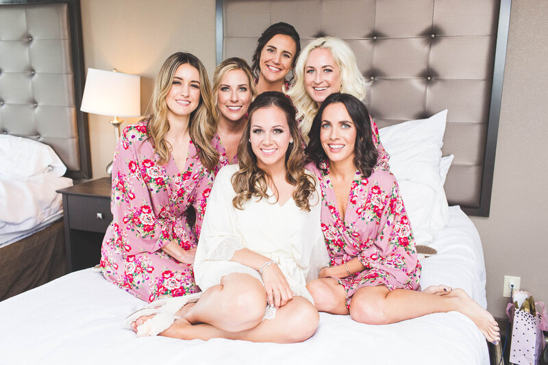 bridal-party-posing-in-robes-on-bed-ohio