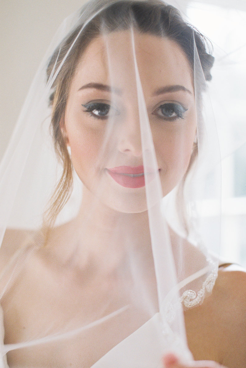 Young woman with cat eyeliner and bold red lips staring at camera in wedding dress holding veil over her face