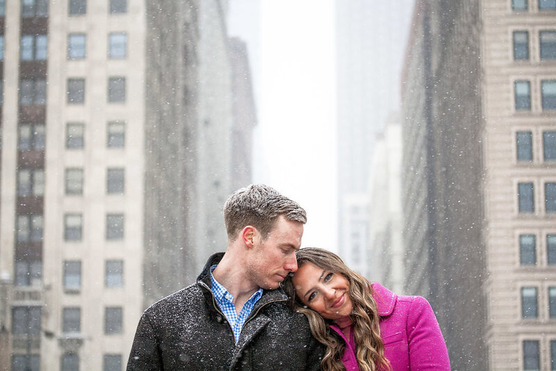 couple walk woodward during snowy winter detroit engagement session