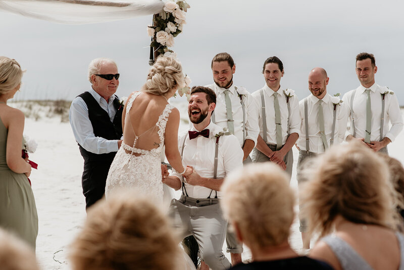 Groom laughing during ceremony on the beach