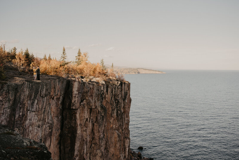 cliff with trees next to water