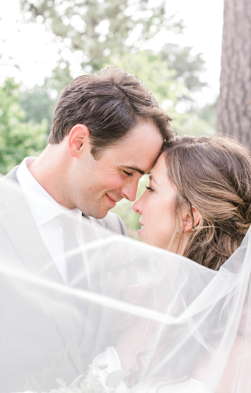 Bride and groom touch forehead with beautiful wedding veil draped