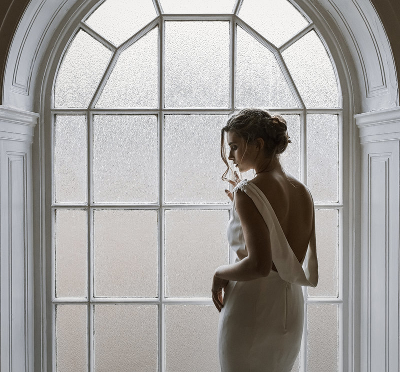 Wedding photography by karl bratby of bride stood by window