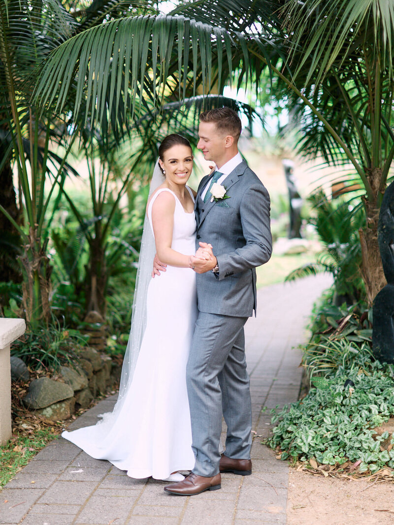 Bride and groom dancing on path under palm leaves