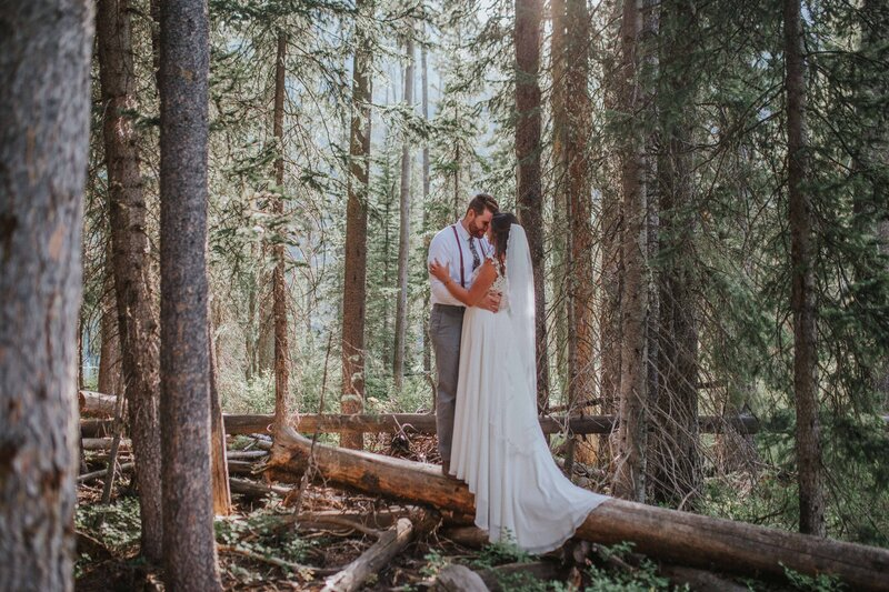 bride with veil and groom with suspenders share their first dance in a forest in a cozy elopement session in gatlinburg