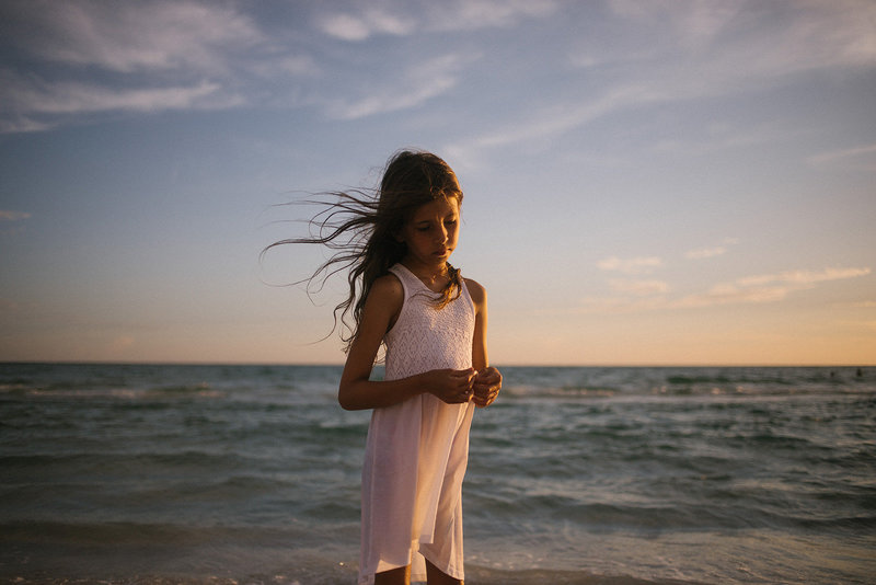 Little girl with long brown hair wearing  white dress on a beach in Siesta Key