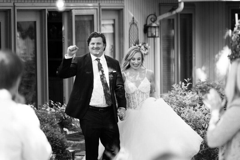 bride and groom celebrate entering wedding reception