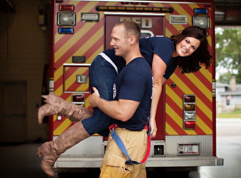Fire fighter is carrying his fiance' over his shoulder.