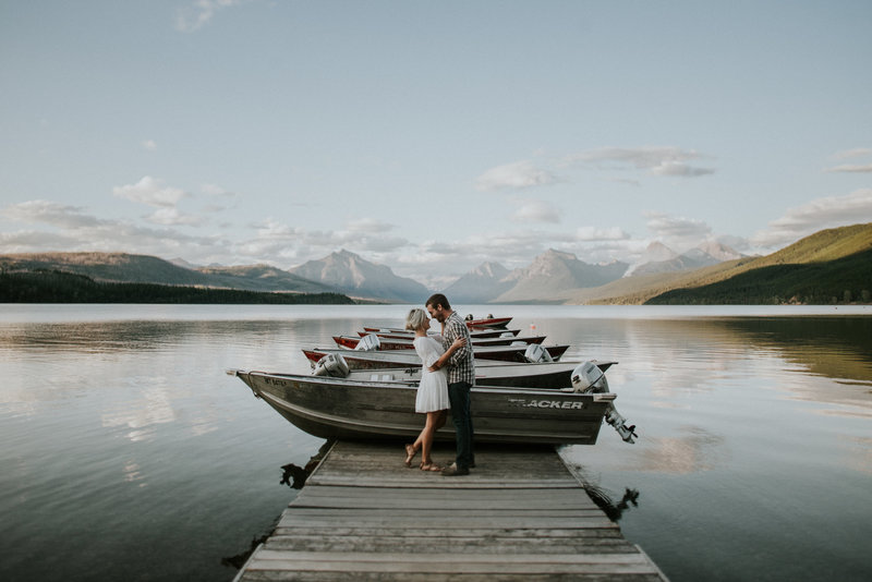 Glacier National Park Engagement Couple Embracing on Dock
