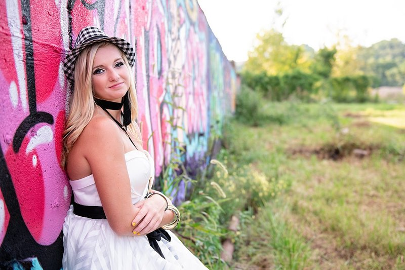 High school senior girl in black and white checked hat and white tiered dress leaning on pink graffiti wall at Carrie Furnace in Pittsburgh, PA