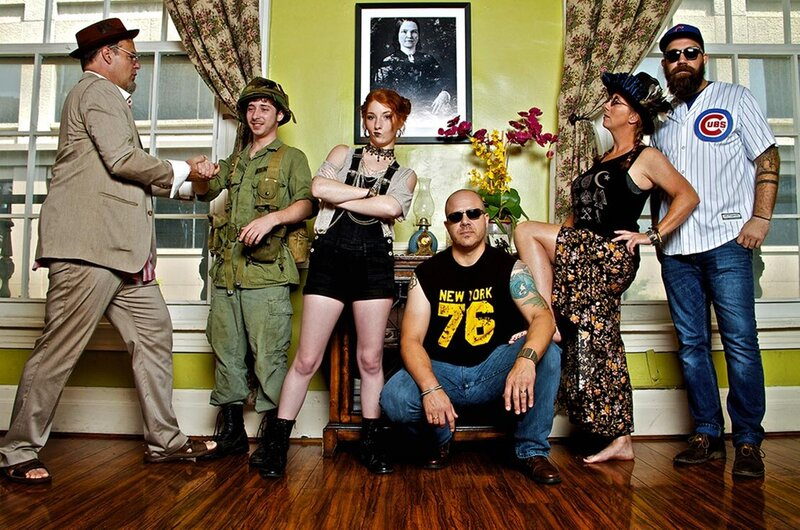 Nashville band photo Amelia Eisenhauer And The Peruvian Farm Girls six band members standing against lime green wall with patterned curtains