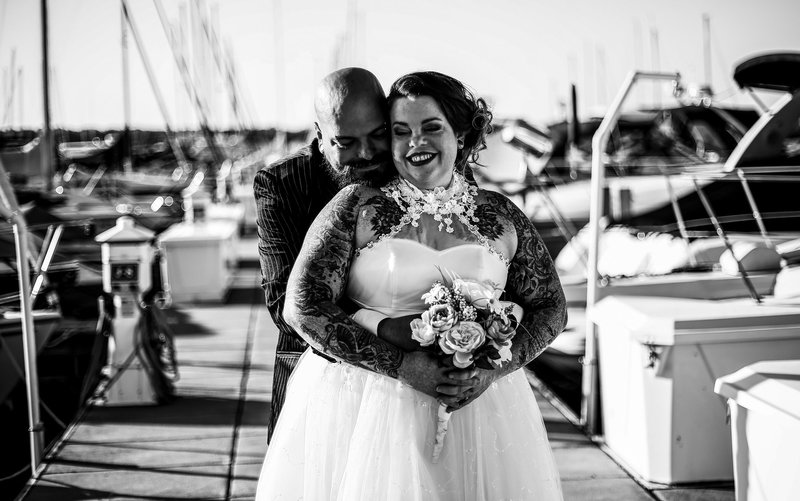 Groom embraces bride on the transient docks of the Erie Yacht Club