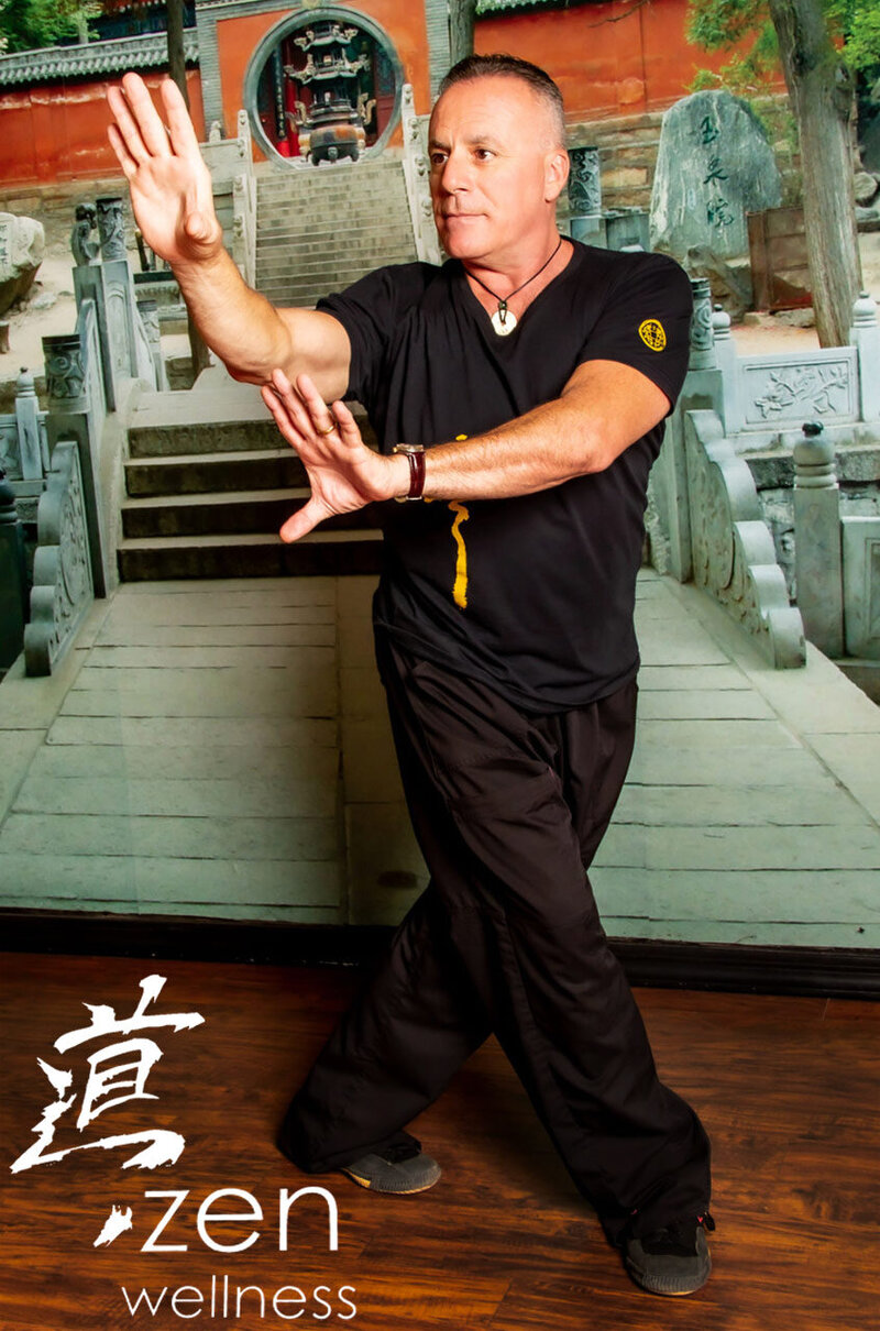 Portrait of Zen Wellness teacher Mike instructing stance in front of photo of temple on wall behind him