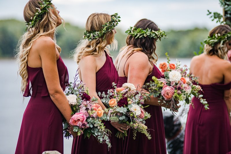 Wedding party bouquet with rich jewel tones in burgundy, coral and deep pink featuring Alaskan peonies, garden roses and local foliage
