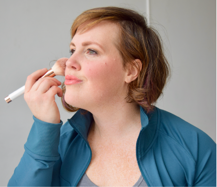 woman using makeup brush putting non-toxic makeup up